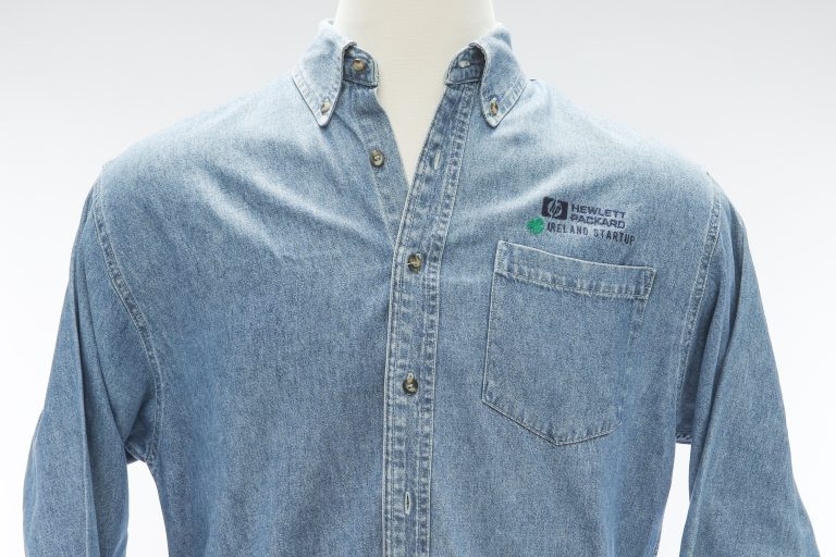 A jean shirt featuring the HP logo and Ireland Startup with a green clover above the pocket.