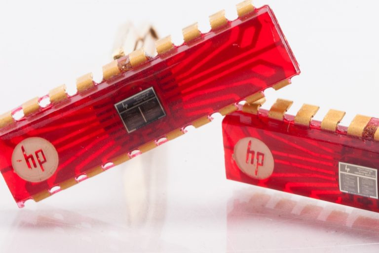 Two gold HP cufflinks with red chips and company objectives printed on a tiny chip in the center of each one.