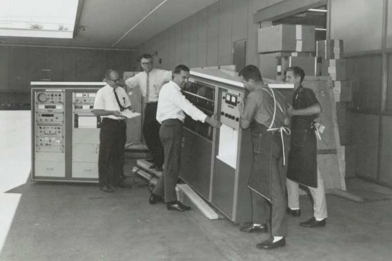 Employees moving the HP 8400A microwave spectrometer in 1964.