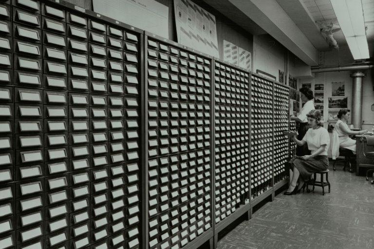 Three women working the name bank card catalog.