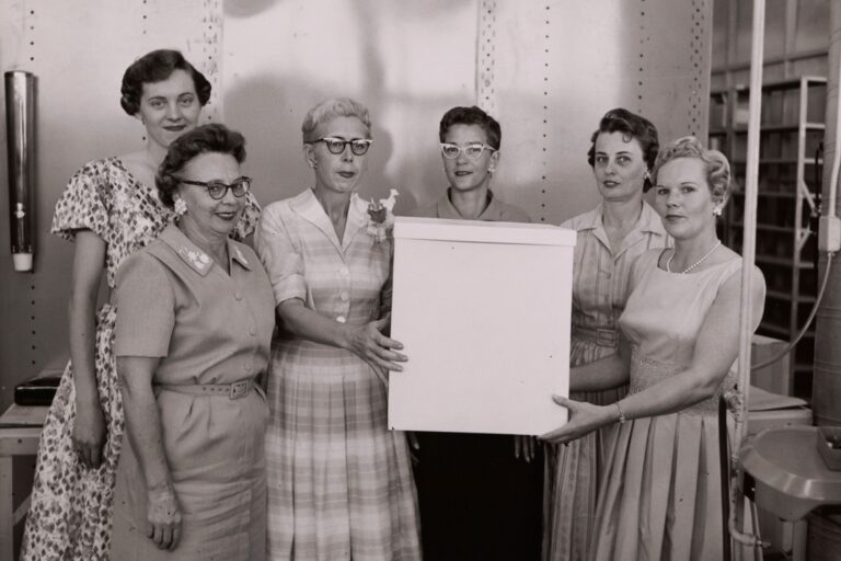 Photo of several women gathered at a celebration and two women holding a large white box.