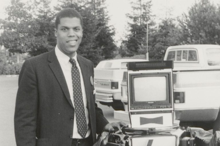 An HP employee poses next to a robot featuring the HP logo on its chest and a monitor for a head.