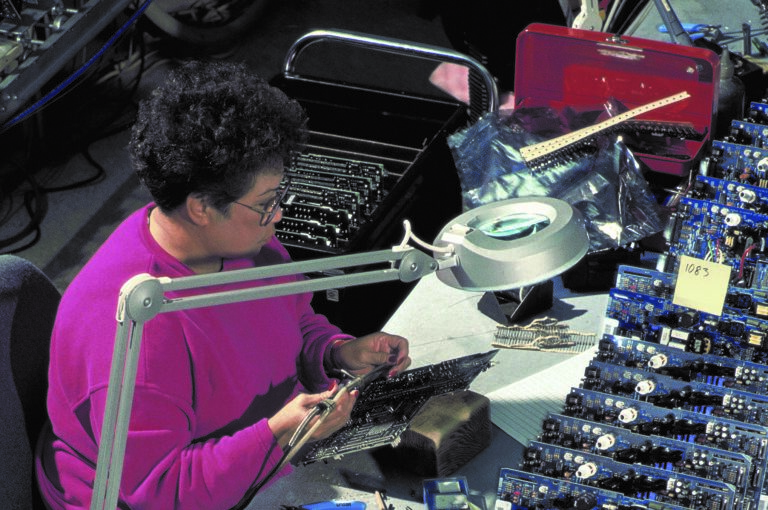 A woman works on a circuit board at the Roseville manufacturing facility in 1993.