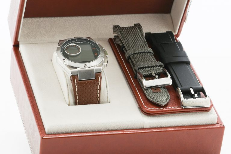 The Michael Bastian smartwatch in its box (opened) with additional strap options.