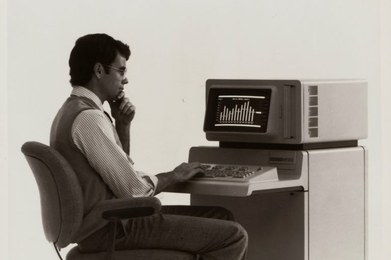 A man sitting at the HP 300 terminal with built-in desk and keyboard.