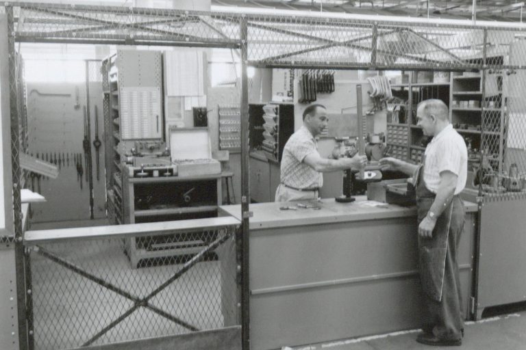 Photo of the Hewlett-Packard toolroom taken in 1961. A man behind the counter is handing a tool to an HP worker.