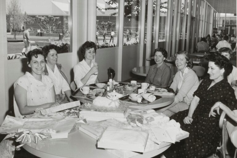Photo of six women gathered around a table during a baby shower in the 1960s.