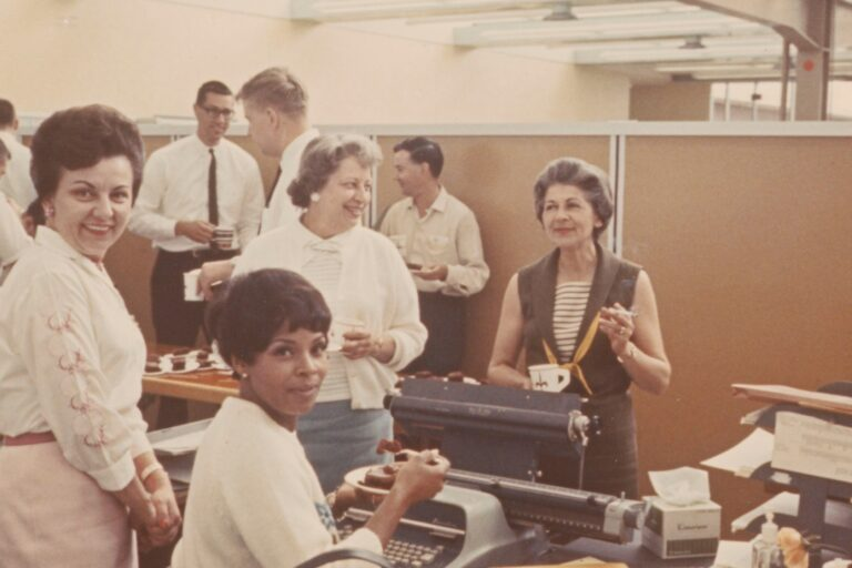 A group of HP employees have cake and coffee in a cubicle in 1964.
