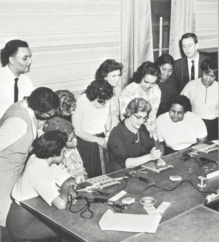 Sanborn plant employees teaching assembly techniques to a group of women at the Cambridge Community Center.