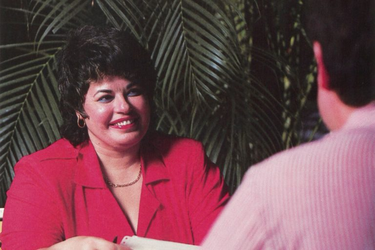 Mabel Esteves seated at a desk opposite a male colleague in 1988.