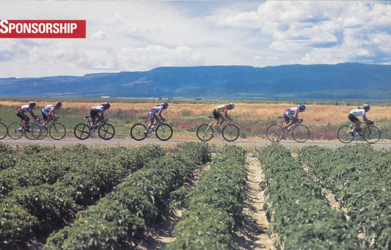 Women cyclists riding on a road near rows of crops.